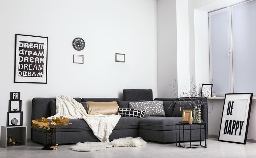 Soggiorno bianco con divano ad angolo nero.