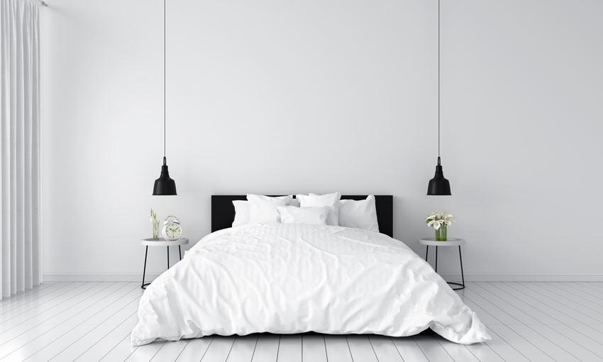 Camera da letto moderna con testiera letto e lampadine sospese nere.