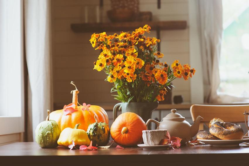 Fiori, zucche e tutti gli ortaggi di stagione sulla tavola in cucina