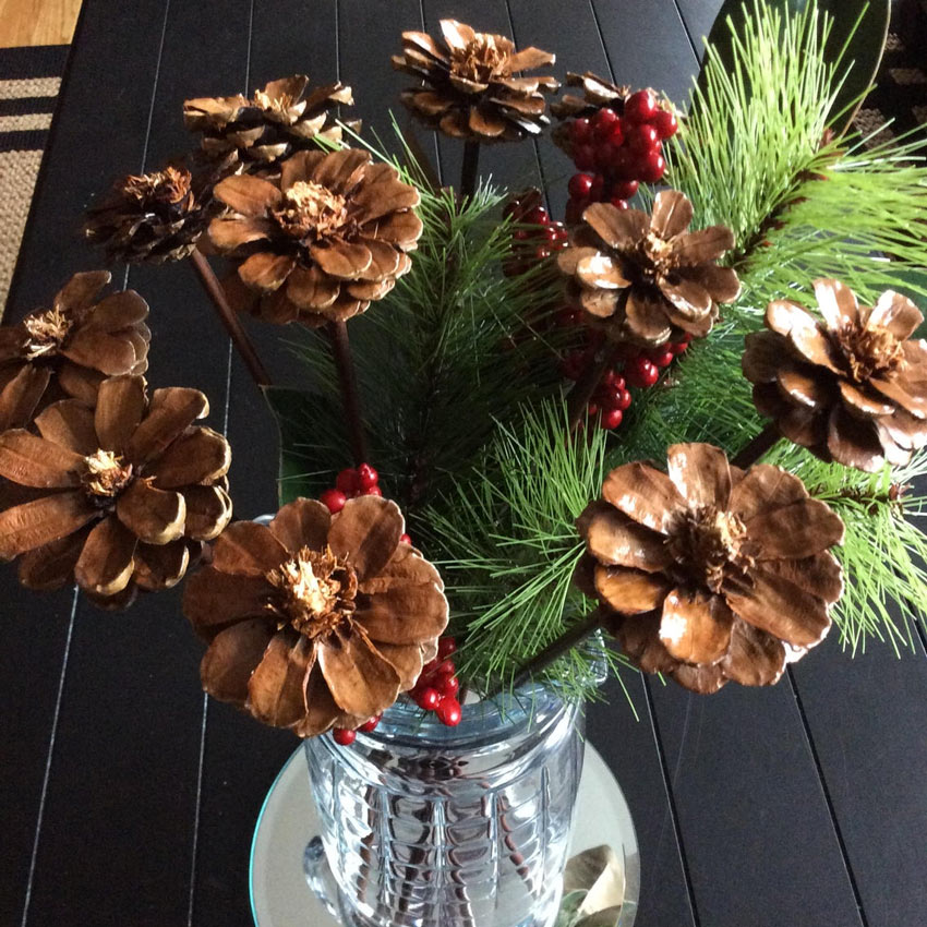 Fiori finti realizzati con pigne in un vaso.