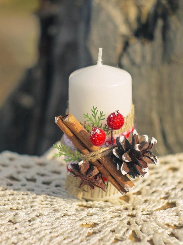 Candela decorata con legnetti e pigne.
