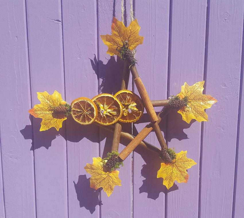 Decorazione autunnale realizzata con legnetti e frutta secca.