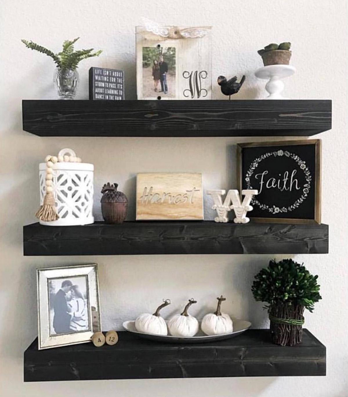 Mensole con tavole di legno nero per arredare una parete