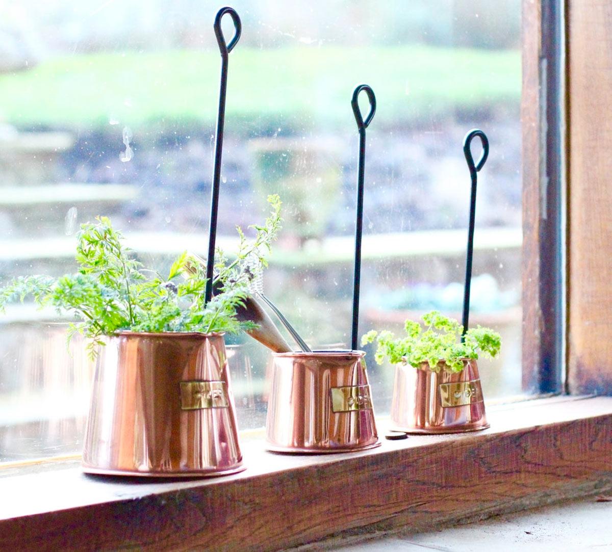 Vasetti in rame con piante aromatiche sul bordo di una finestra.