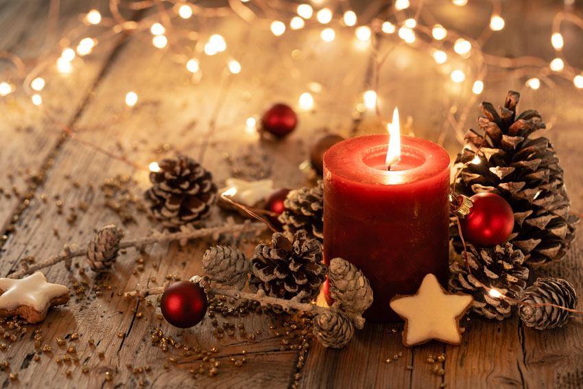 Candela rossa accesa decorata con pigne e palline di Natale.