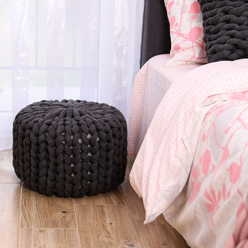 Bel pouf decorativo nero in camera da letto.
