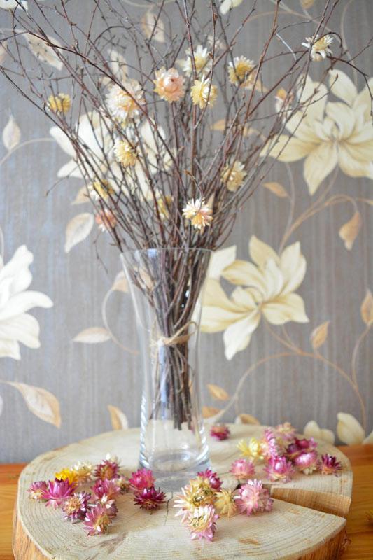 Bel vaso con rami secchi e tronco di legno come sotto vaso.