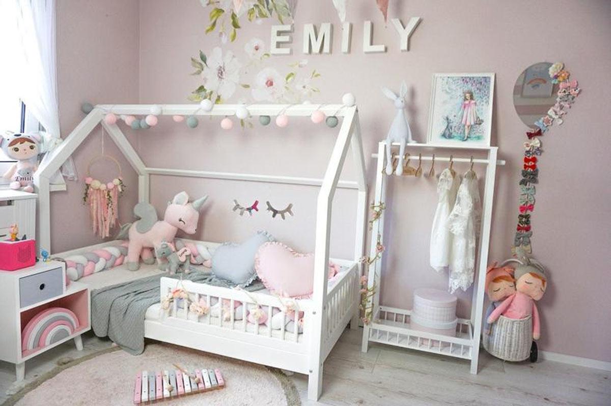 Bellissima cameretta per bambini con letto bianco e pareti rosa.