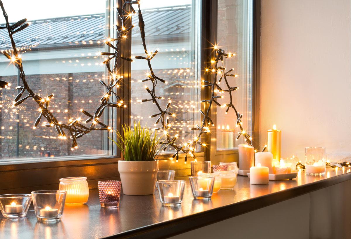 Davanzale finestra decorato con candele e lucette natalizie.