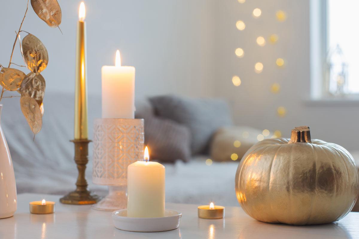 Bellissima composizione di candele con zucca dorata.