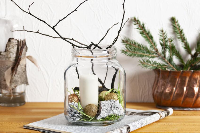 Vasetto di vetro riciclato decorato con rametti, pigne e palline natalizie.