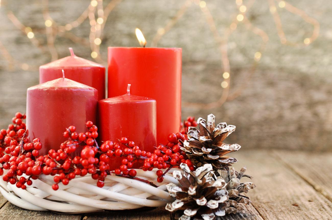 Candele rosse in un cestino bianco decorato con le bacche.