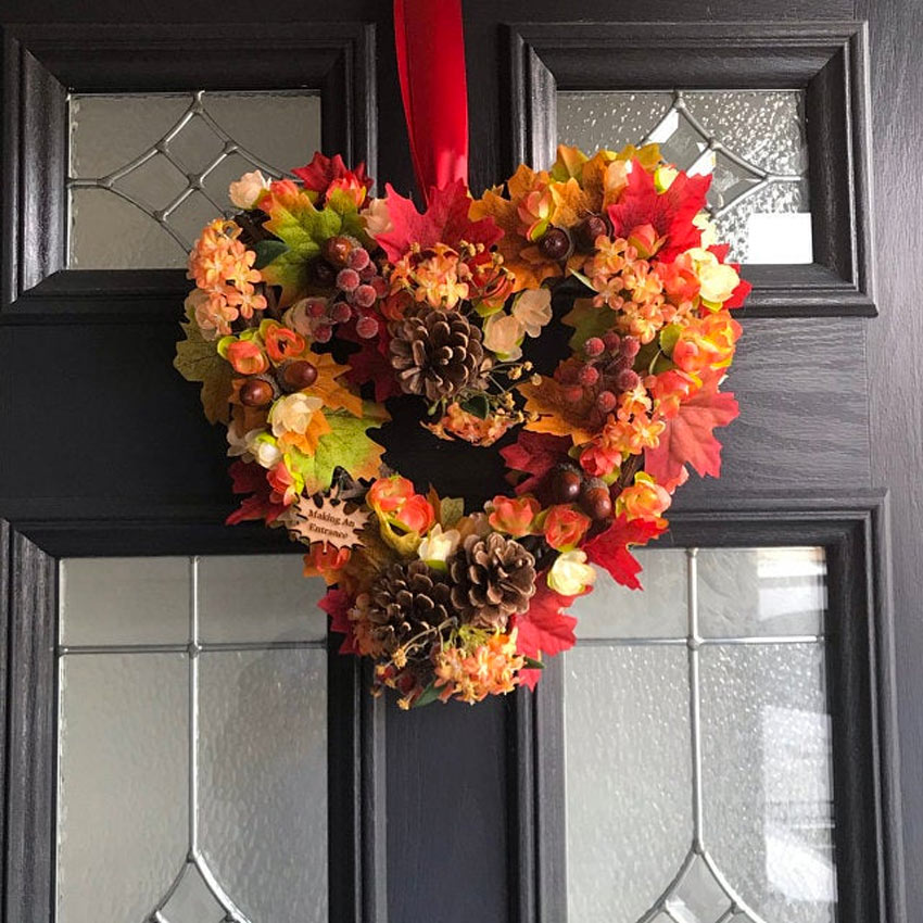 Ghirlanda dietro porta con pigne e foglie secche da realizzare come lavoretto in autunno.