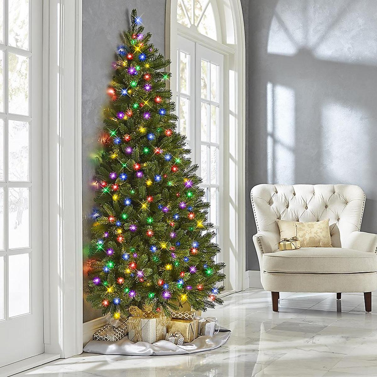 Mezzo albero di Natale con luci collocato su una parete.
