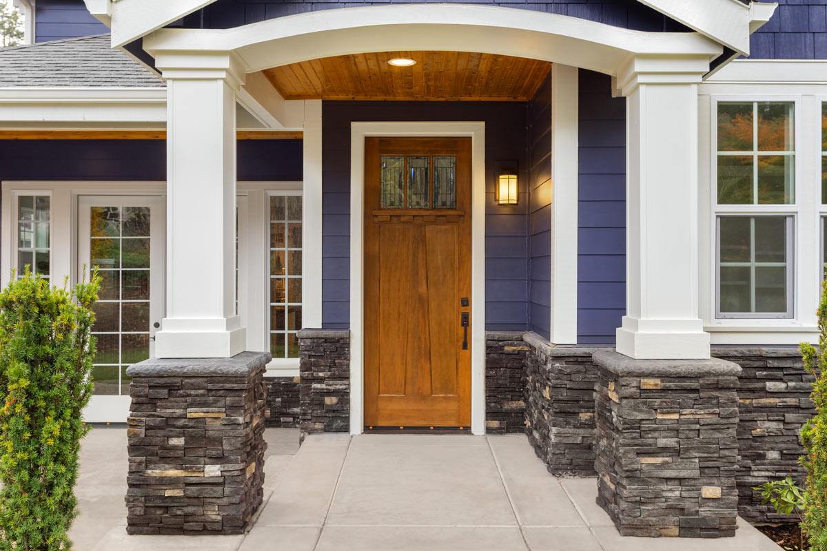 Esterno casa con colonne rivestite di pietre.